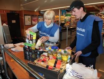 Alguns voluntaris en un supermercat de Llagostera, adherit a la campanya de recollida d'aliments. Foto:JOAN SABATER
