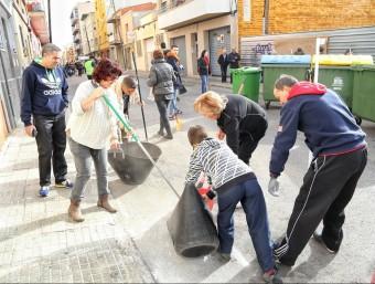 Els veïns i membres de la brigada'empresa municipal fent conjuntament tasques de neteja al carrer Historiador Cardús ahir al matí. Foto:ANDREU PUIG