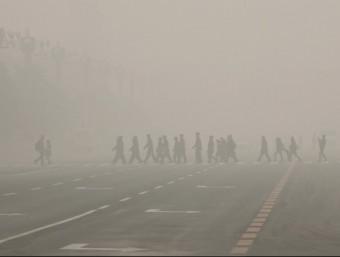 Diverses persones travessen un pas de vianants a la plaça Tiananmen, aquest dilluns a Pequin Foto:REUTERS