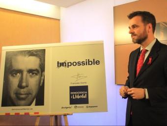Jordi Cuminal, director de campanya de Democràcia i Llibertat, amb el cartell Foto:ACN