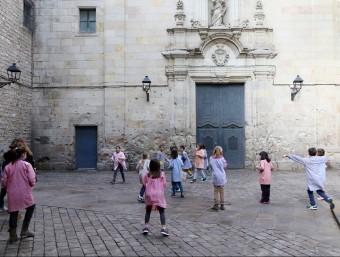 Un grup de nens de l'escola Sant Felip Neri juga a la plaça que du el mateix nom. Són davant de la façana de l'església, on es poden apreciar els forats causats per la metralla Foto:ANDREU PUIG