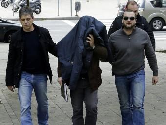 Joaquín Benítez , tapat amb la jaqueta i acompanyat de tres mossos, ahir al jutjat Foto:EFE