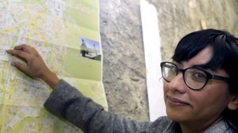 L'artista Amanda Gutiérrez assenyalant un mapa de Girona, ahir en el seu estudi instal·lat a La Mercè Foto:MANEL LLADÓ