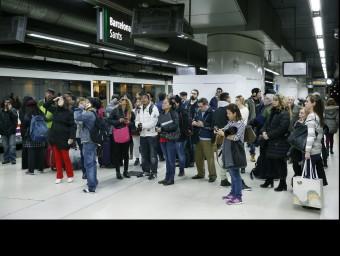 Usuaris observant els panells informatius a l'estació de Sants. Foto:EFE