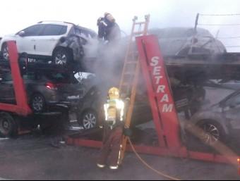 Un efectiu dels Bombers revisa el camió que transportava cotxes incendiat en una àrea de descans de l'AP-7 Foto:ACN