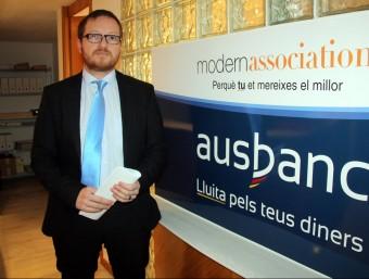 L'advocat d'Ausbanc a Girona, Marc Prat, fotografiat ahir al costat d'un cartell d'aquesta associació. Foto:ACN