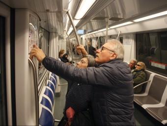 Dos usuaris de la L9 consulten el mapa de la xarxa de metros dins el vagó Foto:ORIOL DURAN