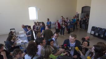 Ferran Bel atén els mitjans mentre els ciutadans fan cua per votar a Remolins. JOSÉ CARLOS LEÓN