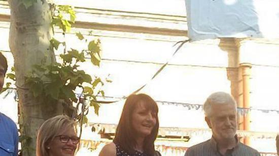 La regidora de Cultura, l'autoa i l'alcalde amb el cartell retirat.