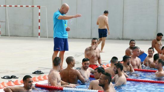 Un grup de reclusos del centre de Brians 2 escoltant les instruccions del monitor de la piscina, divendres s passat al matí Foto:ANDREU PUIG