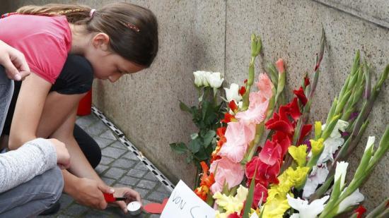 Una nena encén una espelma en record de les víctimes de Munic Foto:REUTERS