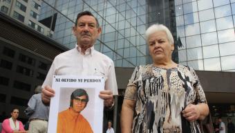 Antonio Martos i la seva esposa, amb la foto del seu germà ahir davant dels jutjats de Sabadell Foto:ACN