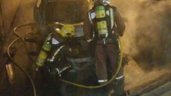 Els bombers en el moment que apagaven les flames que van calcinar totalment el cotxe. Foto:BOMBERS