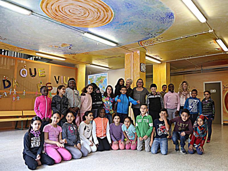 Els alumnes que van participar en el projecte, envoltats per la seva obra, amb LaBGC —que porta una nena en braços—; Pilar de Bolós, al seu costat, i la directora, Laura Serrats Foto:MANEL LLADÓ