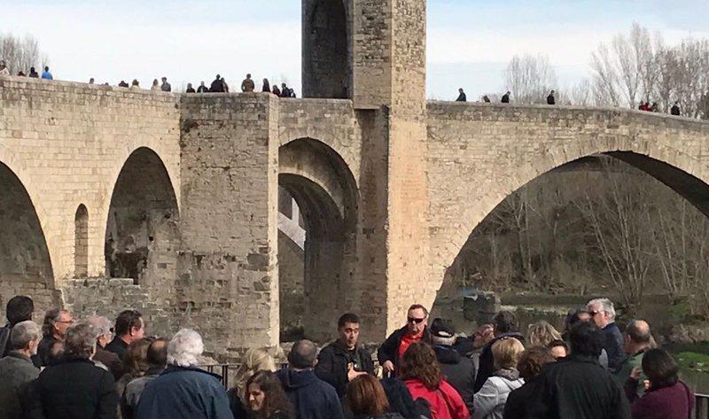 Martí Gironell, al centre de la imatge, durant la visita guiada de diumenge a Besalú, amb el pont al darrere.