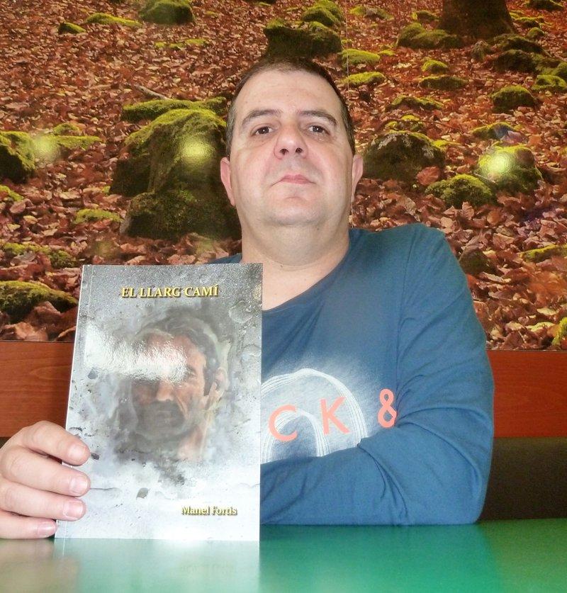 Imatge de Manel Fortis, fotografiat amb la seva última novel·la, una de les més intimistes que ha creat, juntament amb la primera.